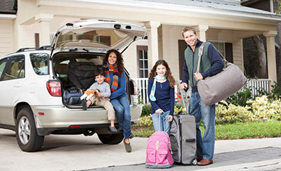 family with luggage sitting in back of suv